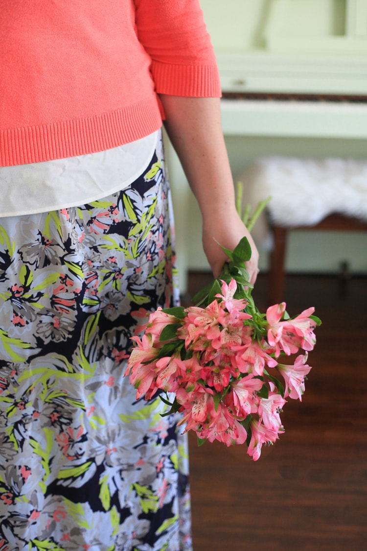 A person in a floral skirt holding a bouquet of pink flowers by their side.