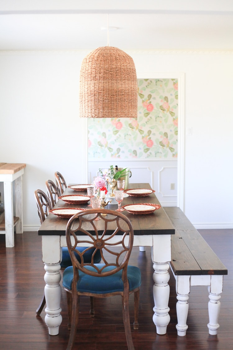 A farmhouse style dining room table set with dishes, with a wicker basket style pendant light above.
