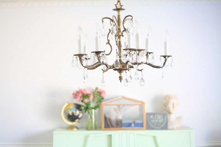 A room featuring a vintage chandelier and a piano covered in Spring decor items.