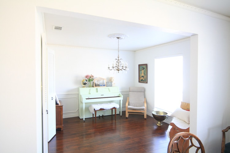 A bright white room with a mint green piano at one end, with Spring flowers atop.