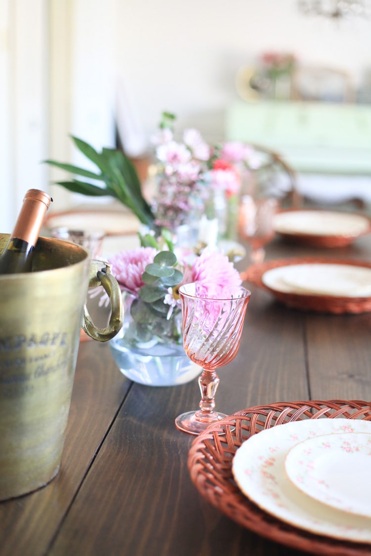 Jars of flowers and Spring inspired dishes on a dining table.