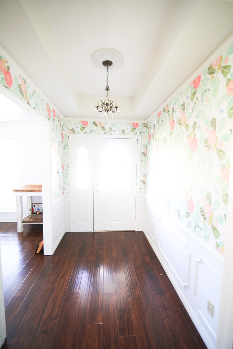 A brightly lit entryway covered in floral wallpaper with pink and green tones.