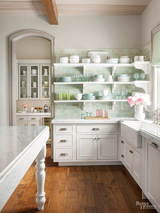 Open shelving in a kitchen with white cabinets and mint subway tile