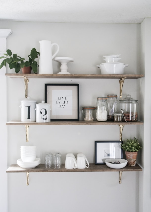 Open kitchen shelves styled simply with white pottery, prints and glassware