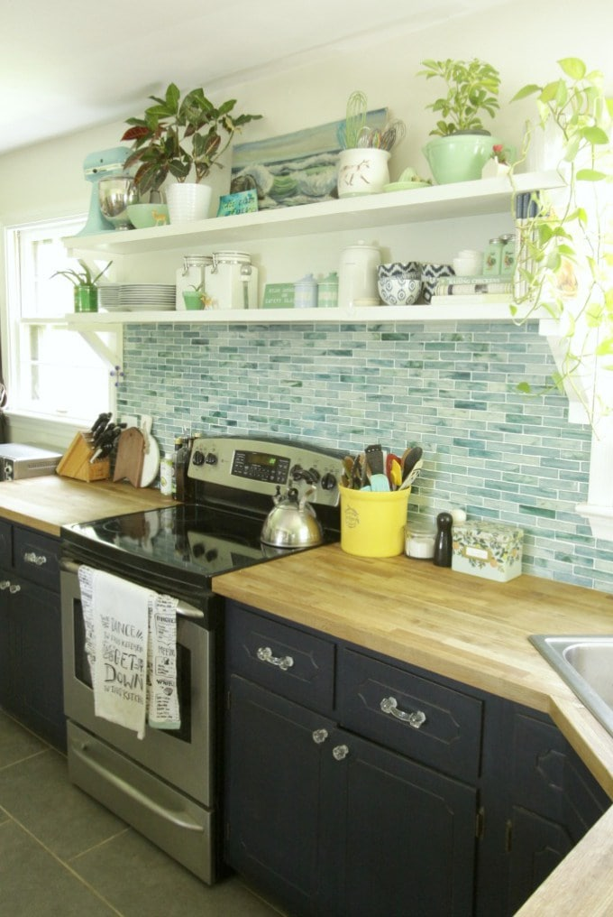 White kitchen shelves holding plants and dishes above a stove with blue tile