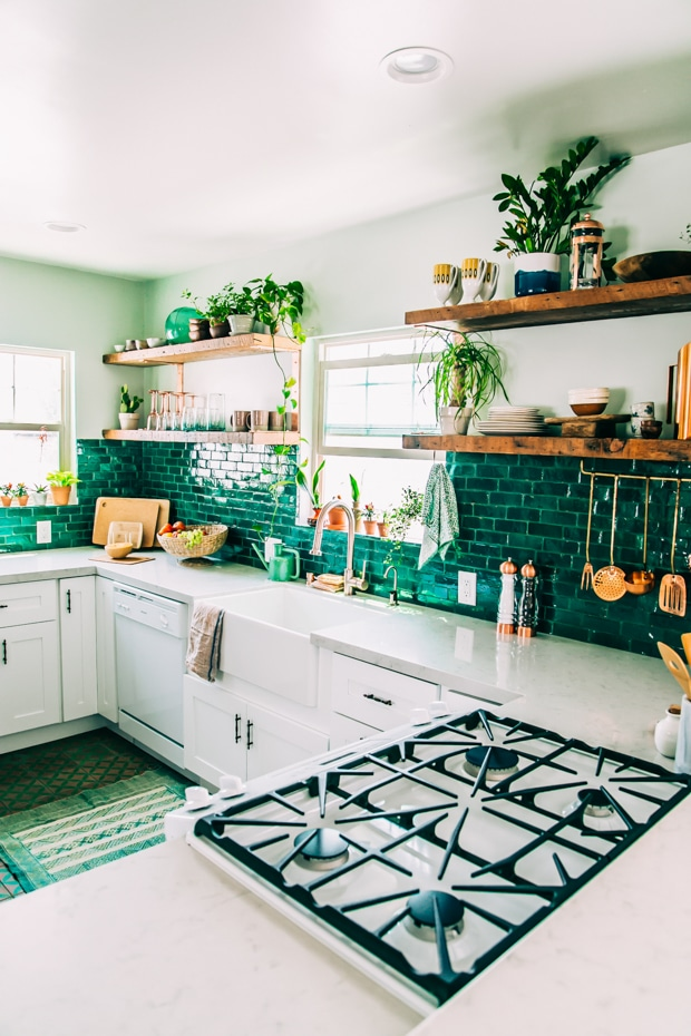 Wooden open shelving in a kitchen with green subway tile