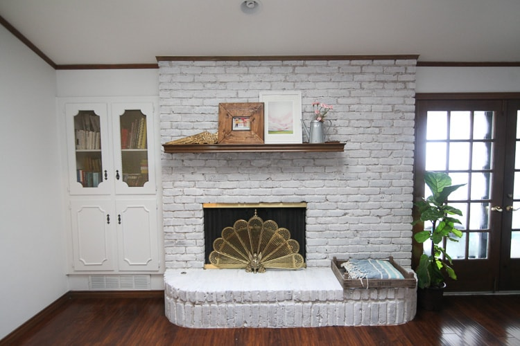 living room with white walls, dark wood floor and a whitewash brick fireplace with wood mantle
