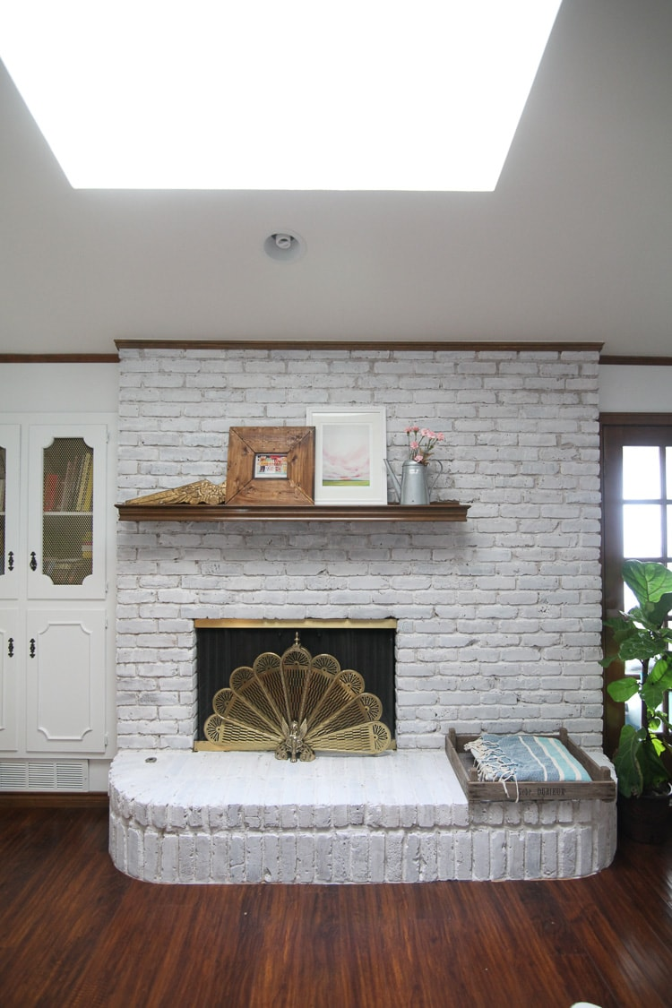 Whitewash brick fireplace with wooden mantle