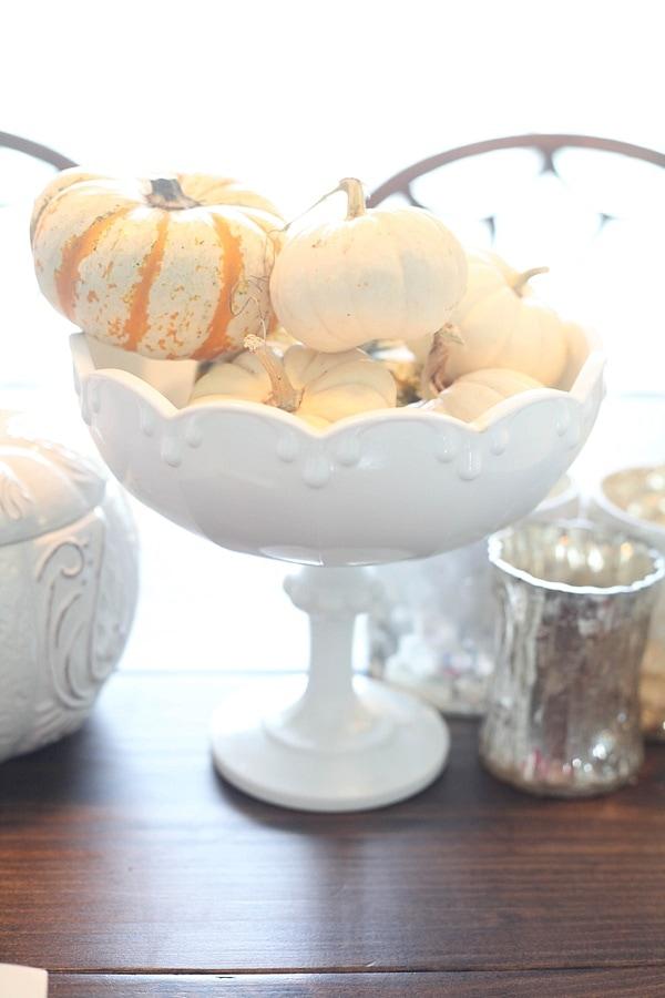 seasonal mini pumpkins on display in a bowl as cheap fall decor