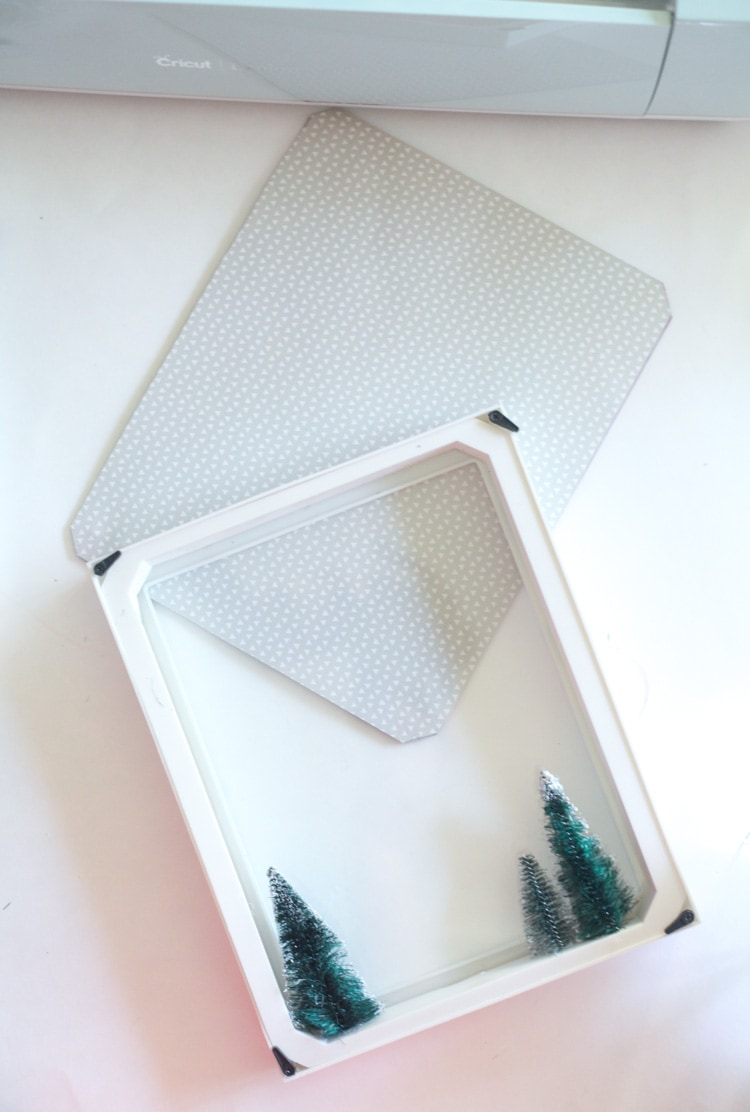 Let it snow! This DIY Christmas shadow box idea is an easy Cricut project for beginners. Super cute! #cricutdiy #christmasdiy #shadowbox #christmasshadowbox