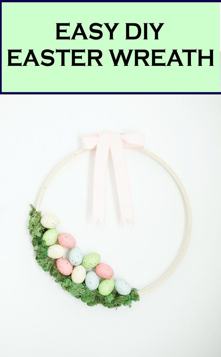 Easter wreath made from an embroidery hoop with moss, pastel colored eggs and a pink ribbon.