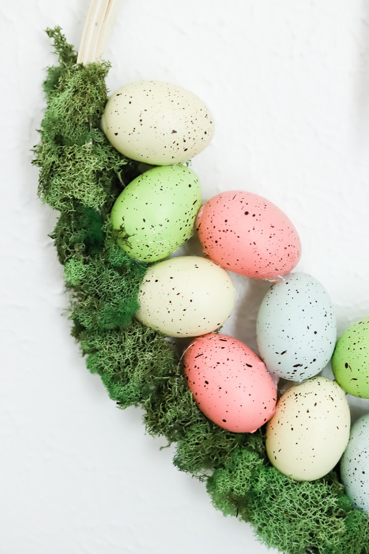 detail shot of pastel colored eggs hot glued onto moss