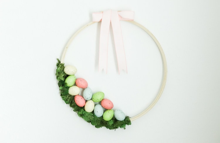 Easter wreath made with an embroidery hoop. Moss is hot glued on the bottom with foam pastel colored easter eggs on top of the moss. There is a pink ribbon tied in a bow on the top of the wreath.