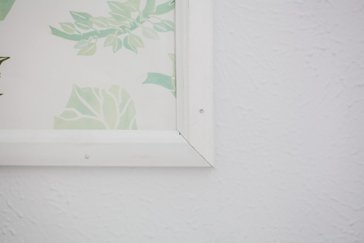 This framed wallpaper in the nursery is so cute! Such a smart idea for what to do with leftover wallpaper—love this framed wallpaper diy and the print on these Anthropologie Watercolor Flora panels!