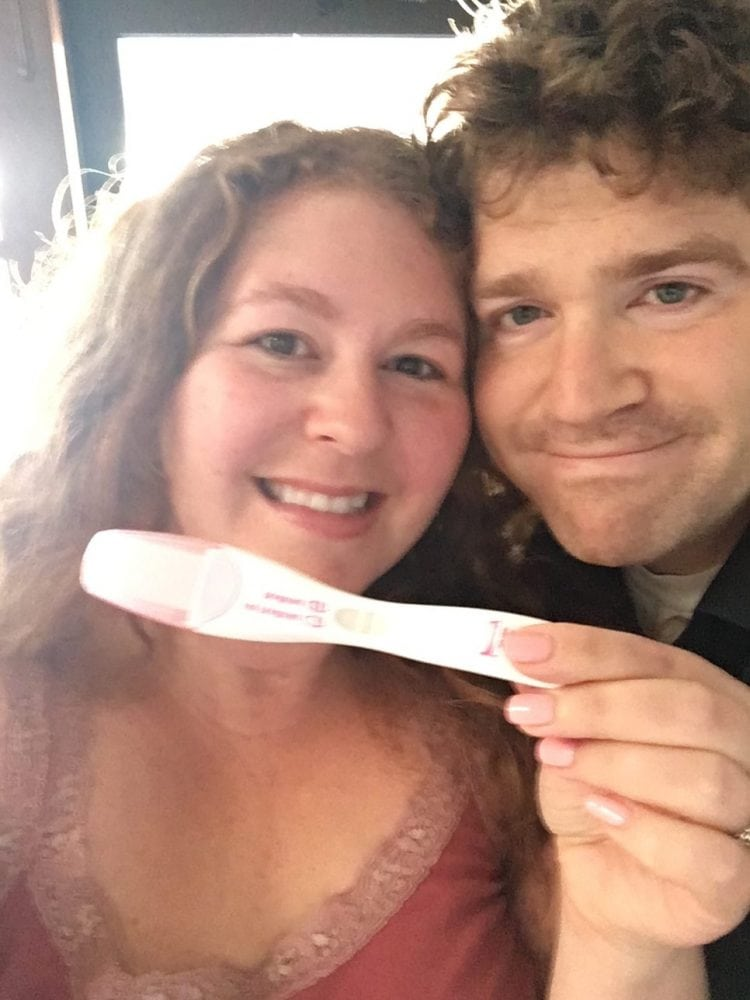 Couple crying with positive pregnancy test