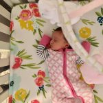 newborn girl asleep in crib