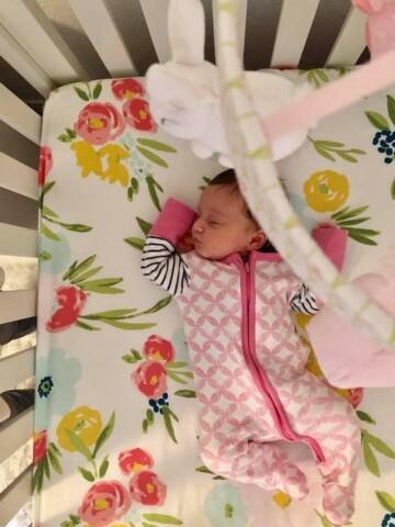 newborn girl asleep in crib