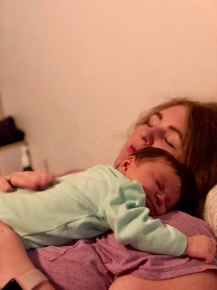 Newborn girl hugging sleeping mom