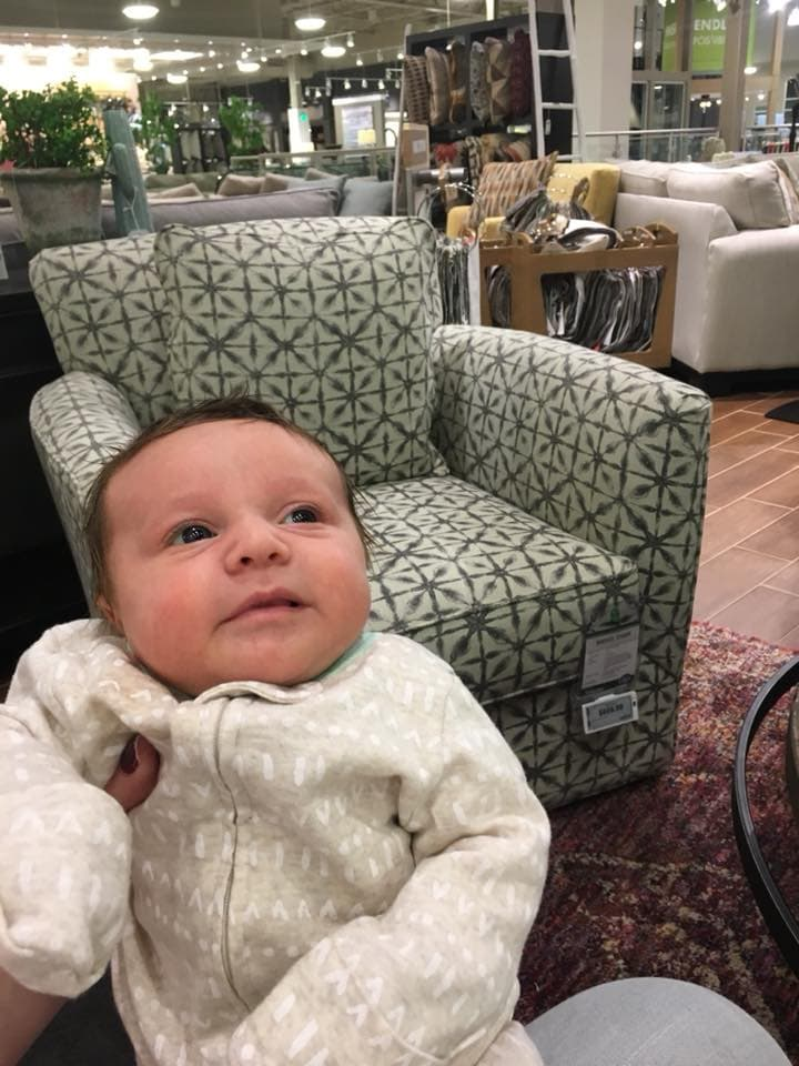 Newborn girl smiling at a furniture store
