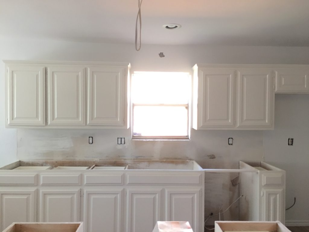row of white painted kitchen cabinets with window
