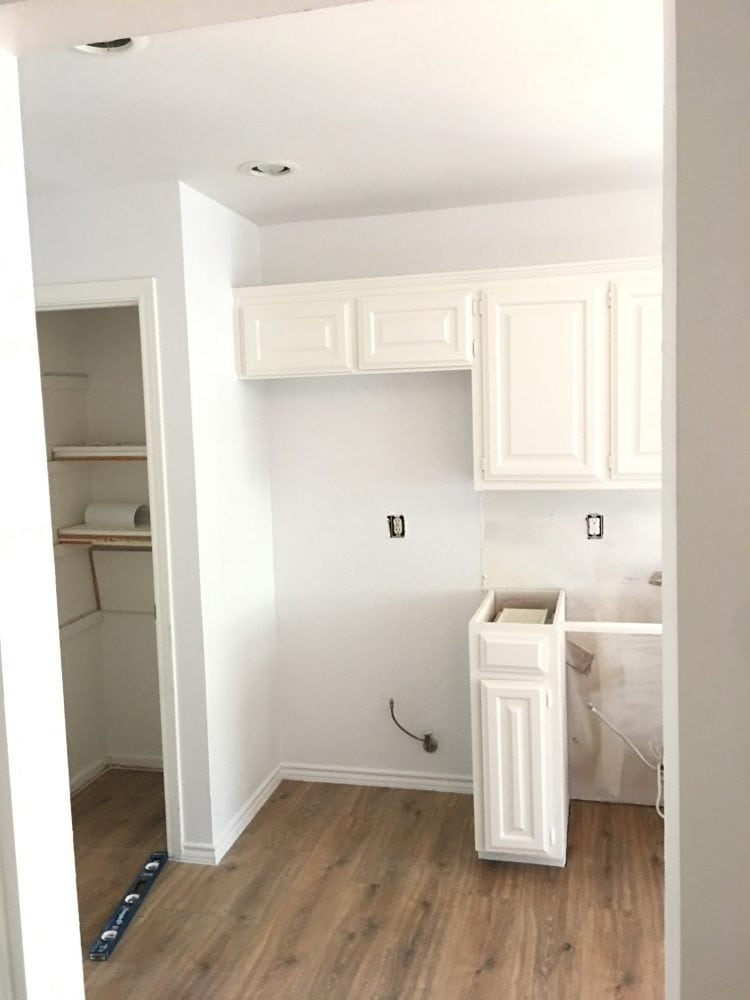 white painted kitchen cabinets with spot for fridge