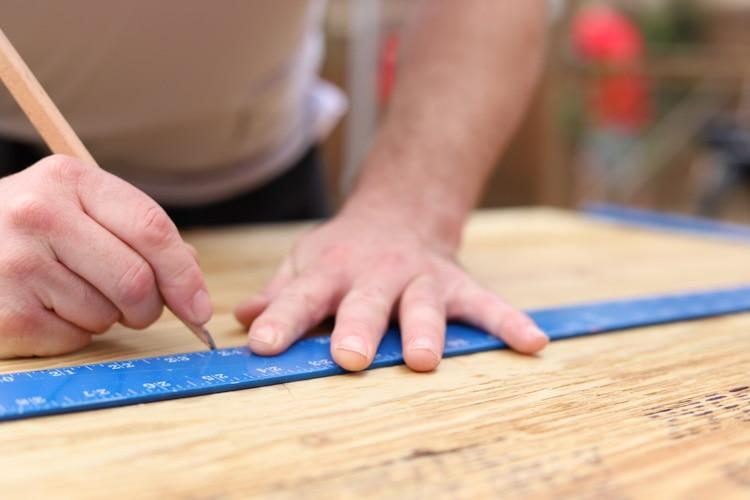 man measuring a plywood board