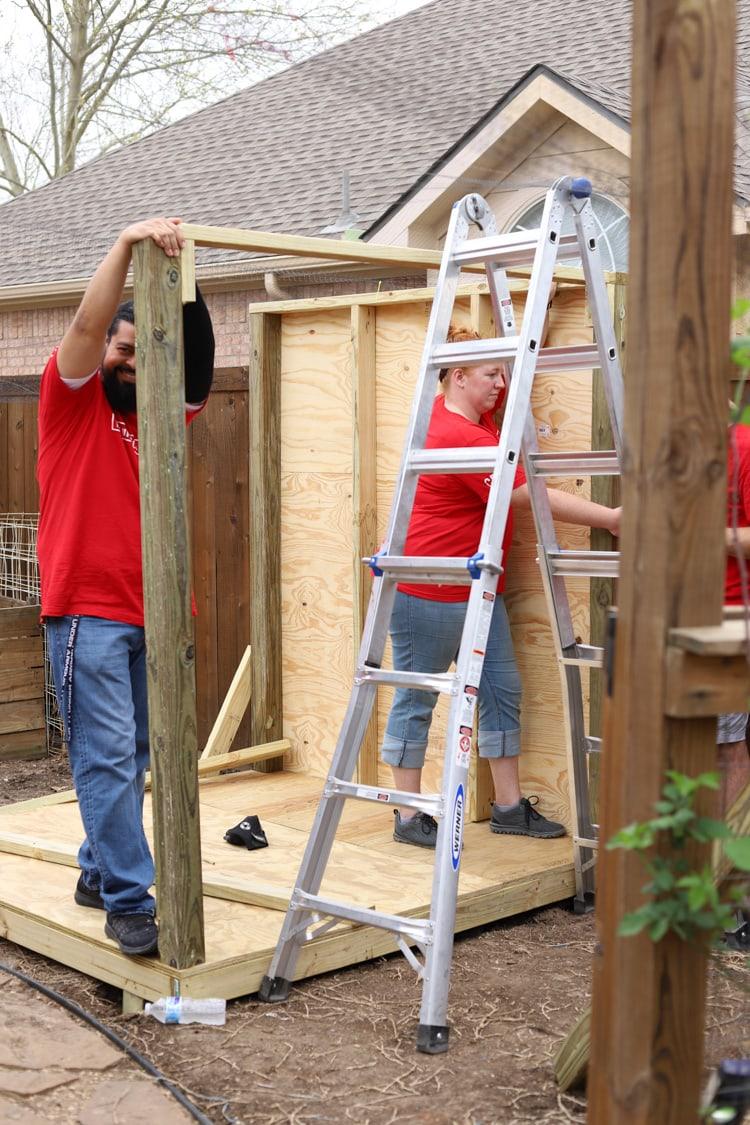 crew building a chicken coop frame