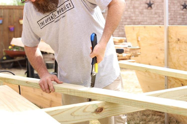 man sawing a 2x4