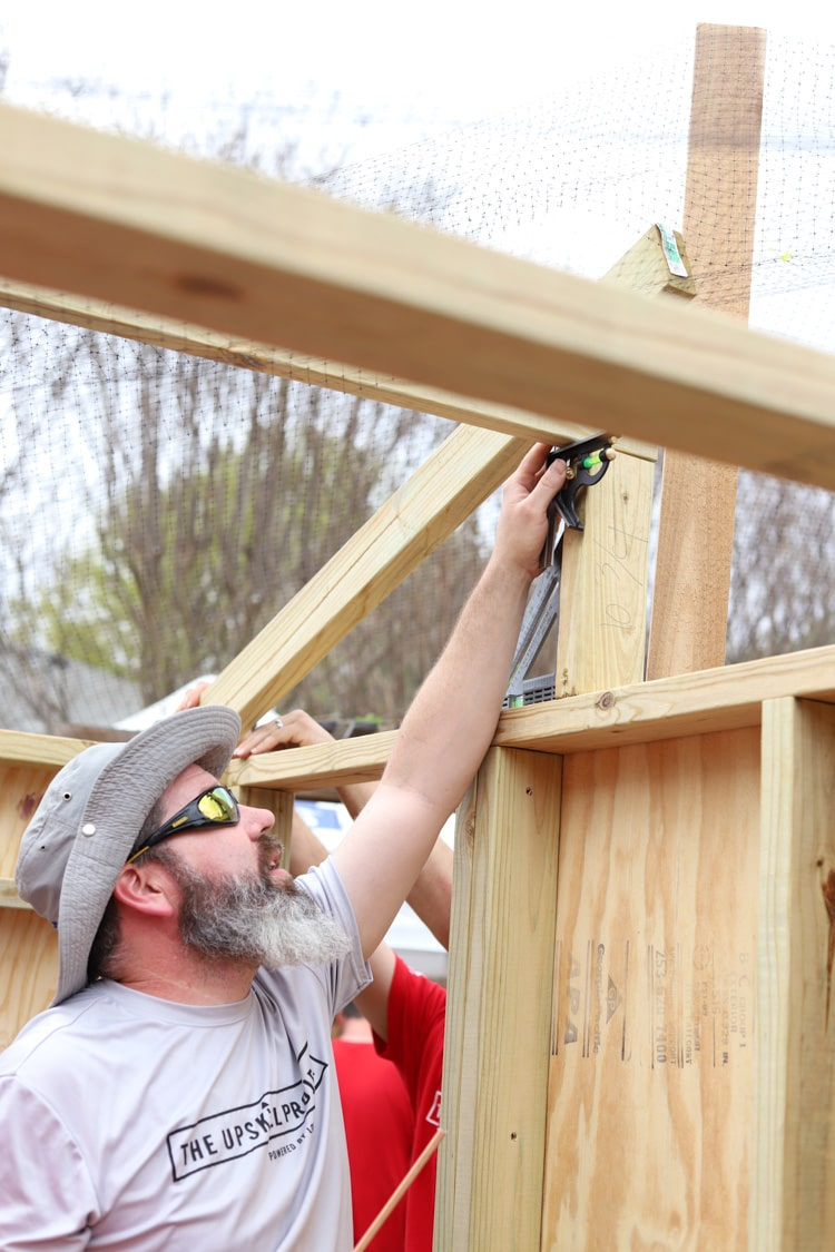 man building chicken coop frame