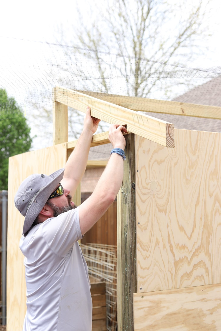 man adding beams to chicken coop roof