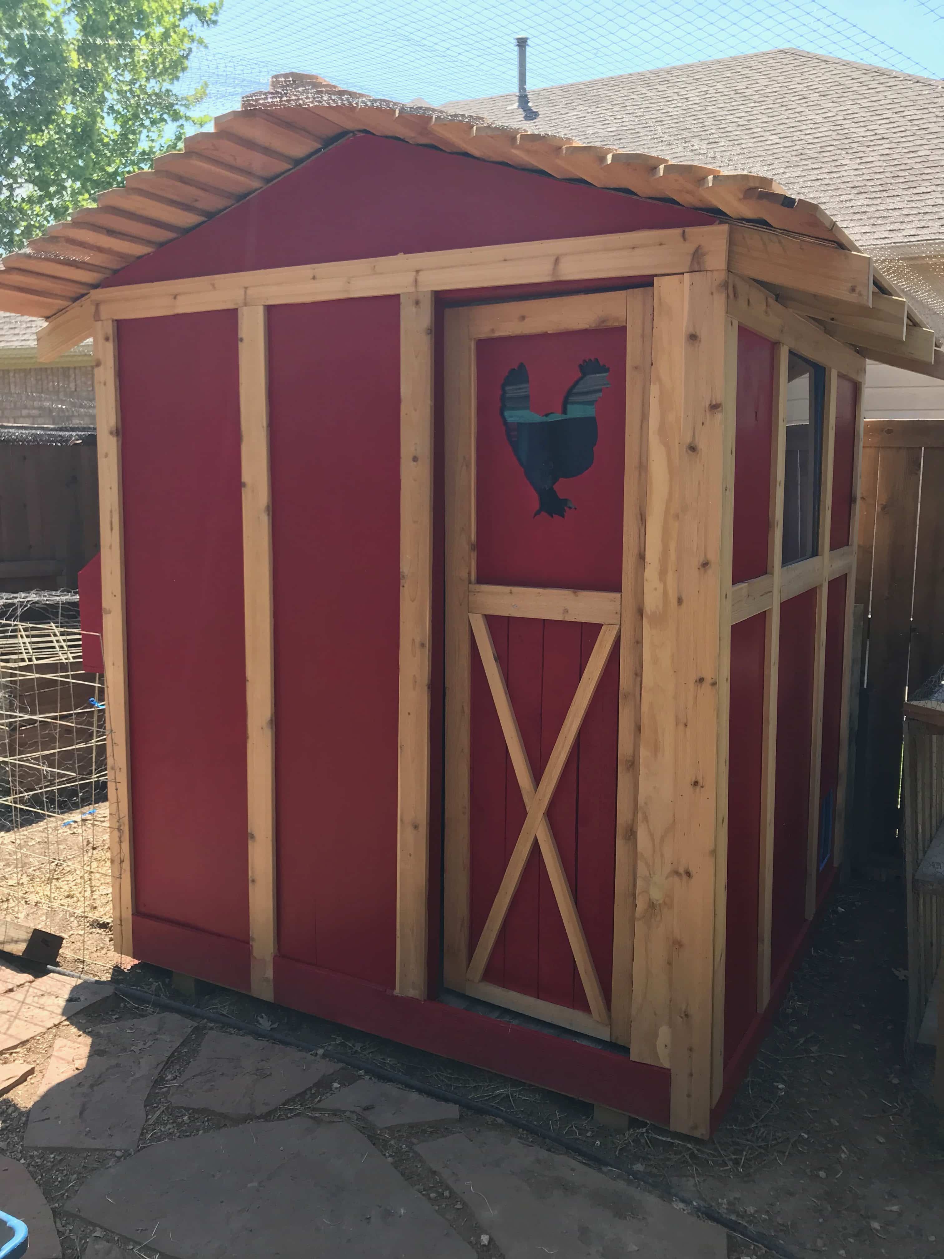 red chicken coop with tin roof
