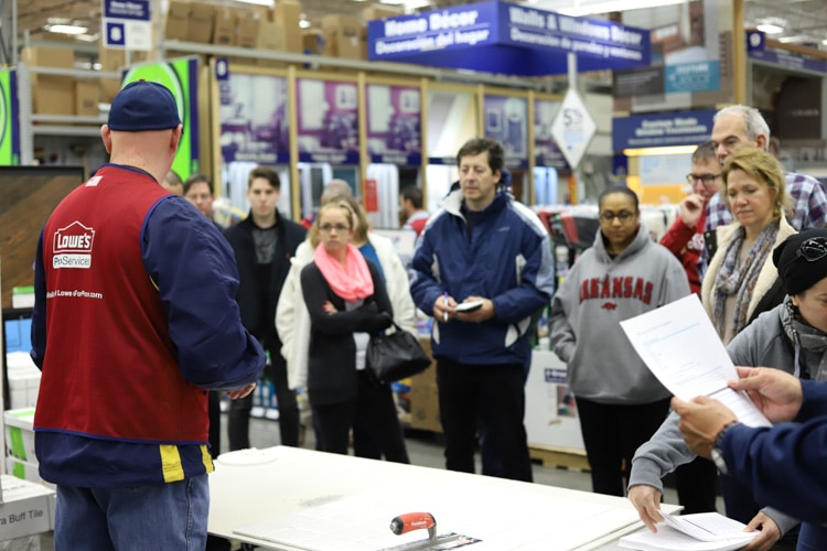 crowd of people watching a tiling demonstration at lowe's
