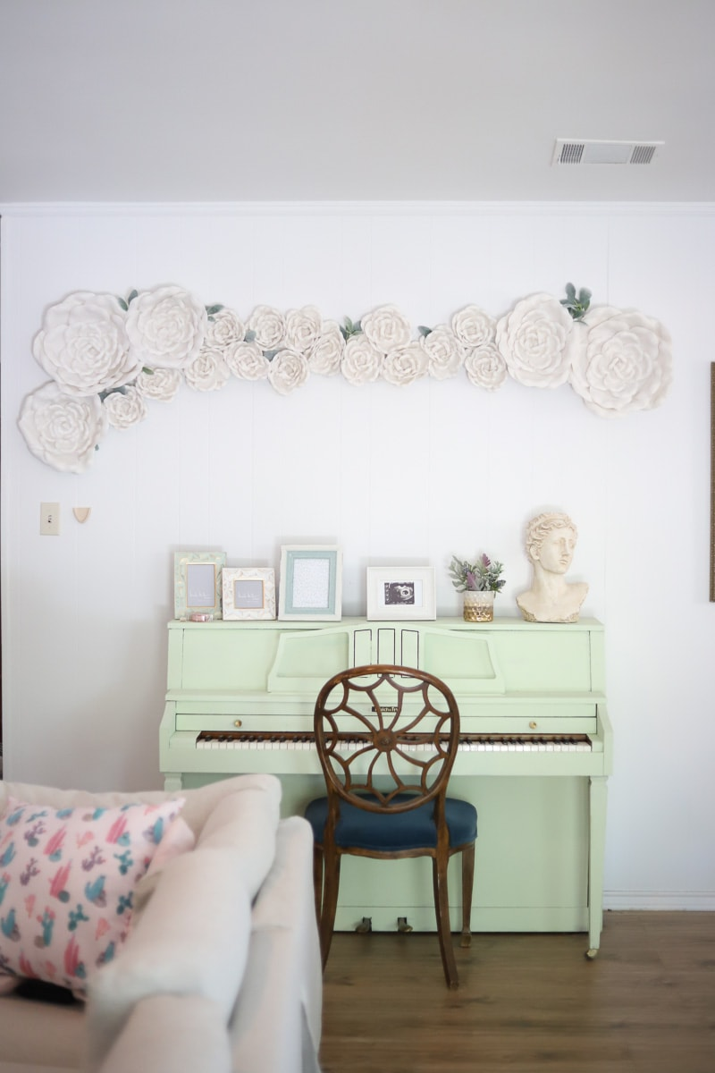White flower wall decor hanging on a living room wall above a mint piano.