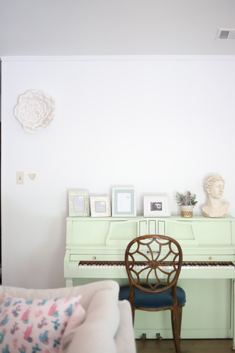 white foam flower hung above a mint piano