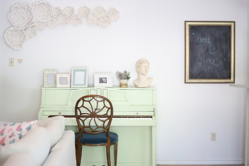 Mint piano with white flower wall decor hung above