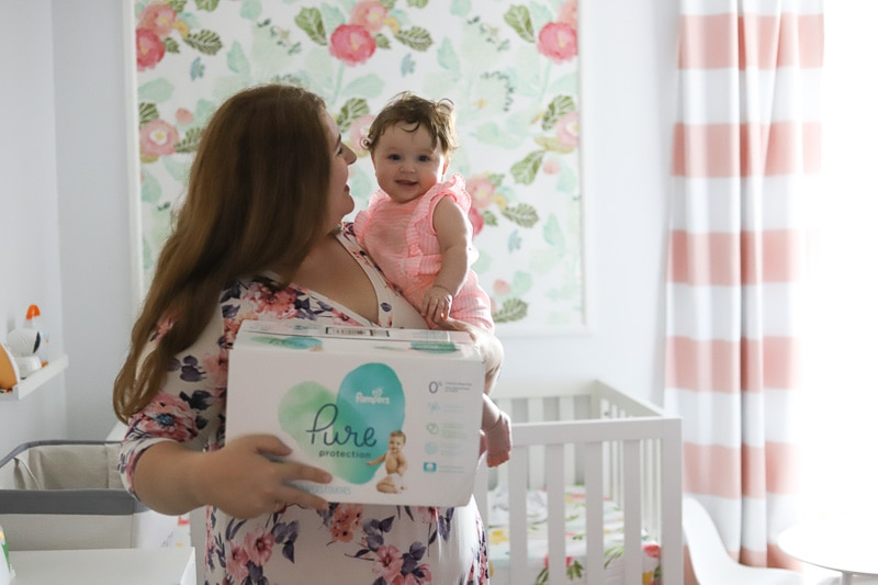 woman holding pamper's pure diapers and baby