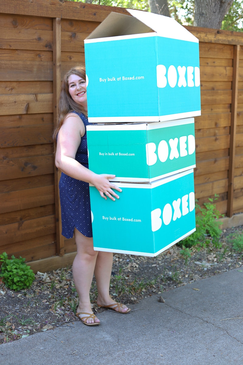 woman holding stack of boxes from boxed.com