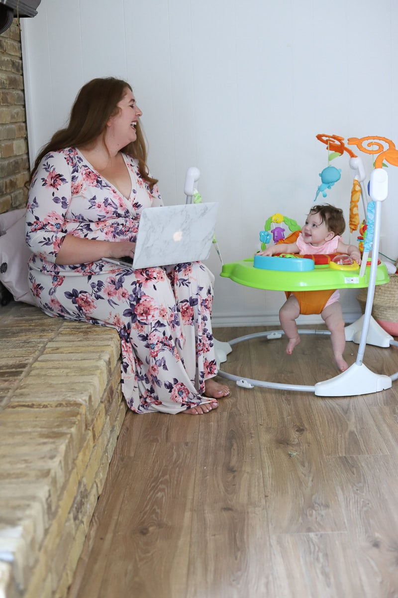 Woman working on laptop while baby plays