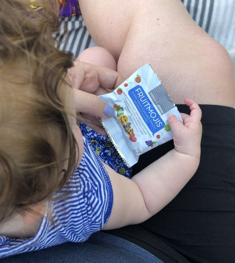 baby holding fruit snack package