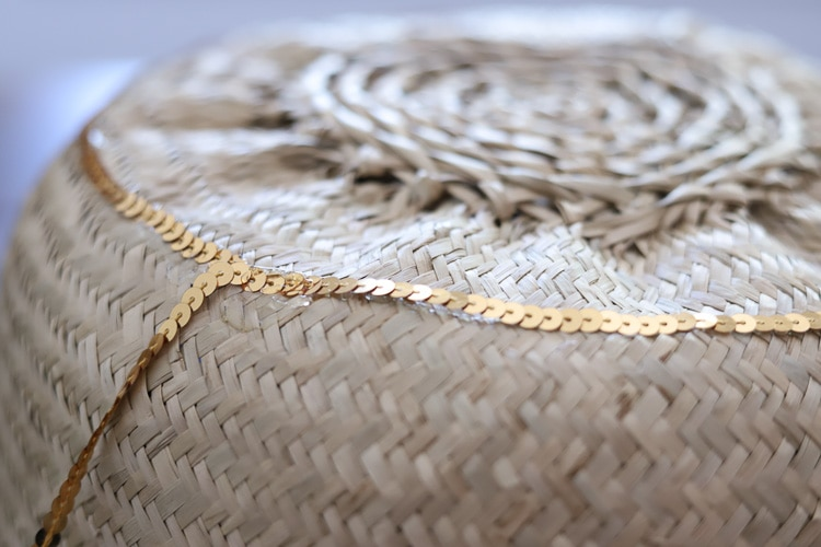 gluing gold trim around wicker basket from ikea