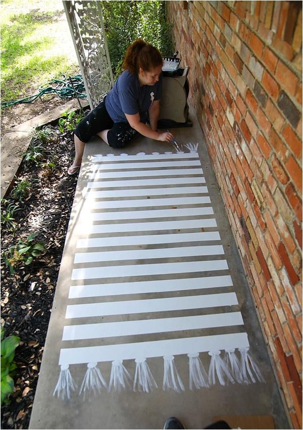 girl painting rug onto concrete patio