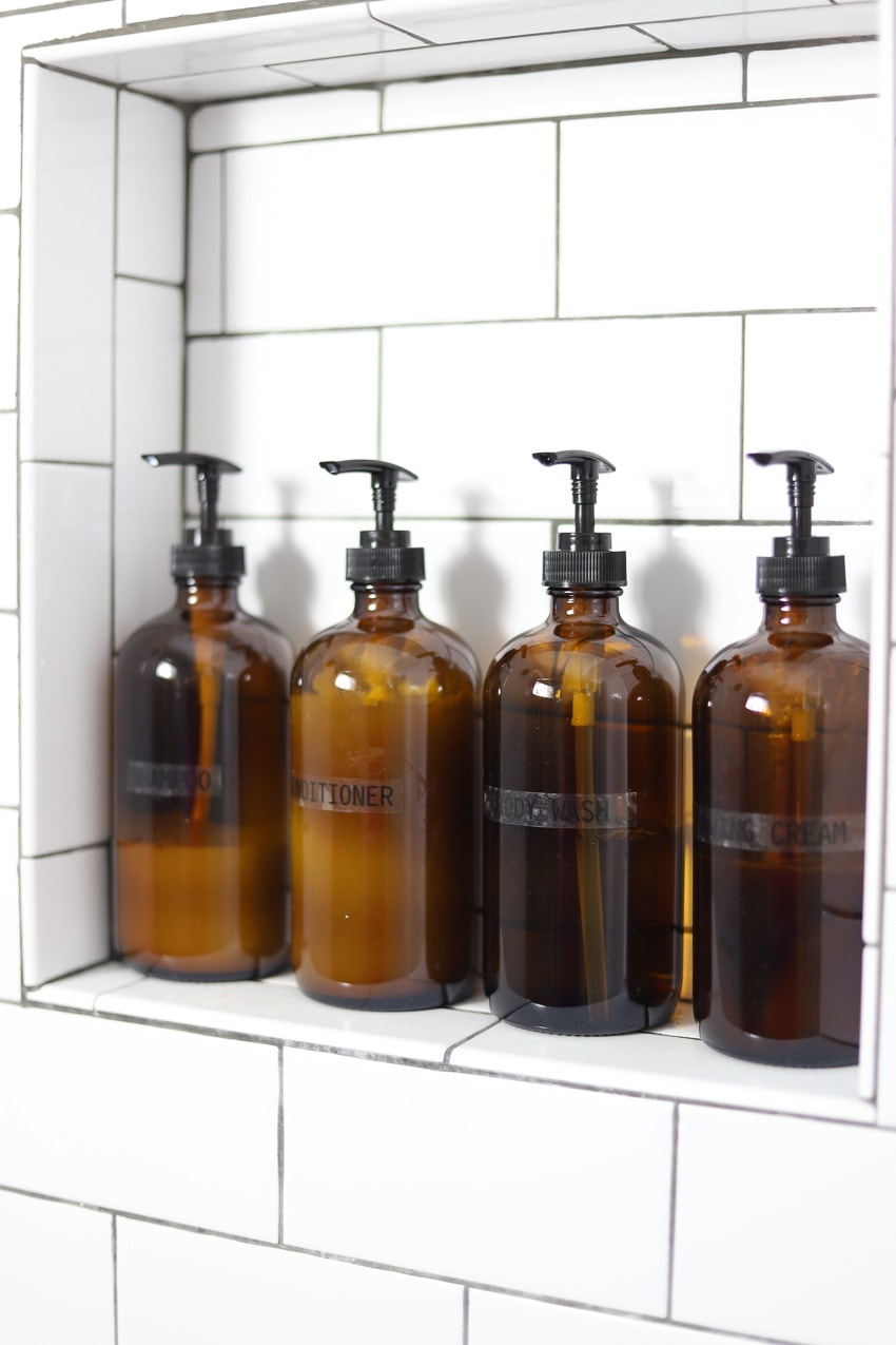 4 amber glass pump bottles for shampoo and conditioner in a shower