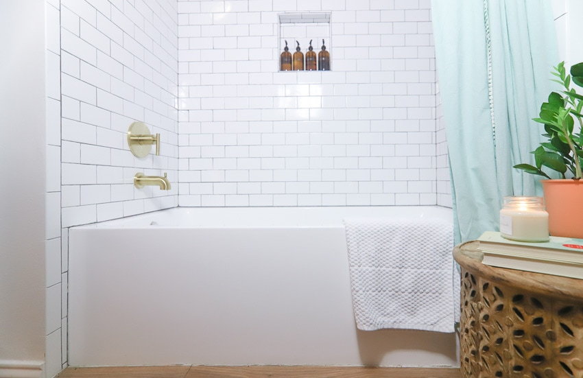 White bathtub with brushed gold shower fixtures