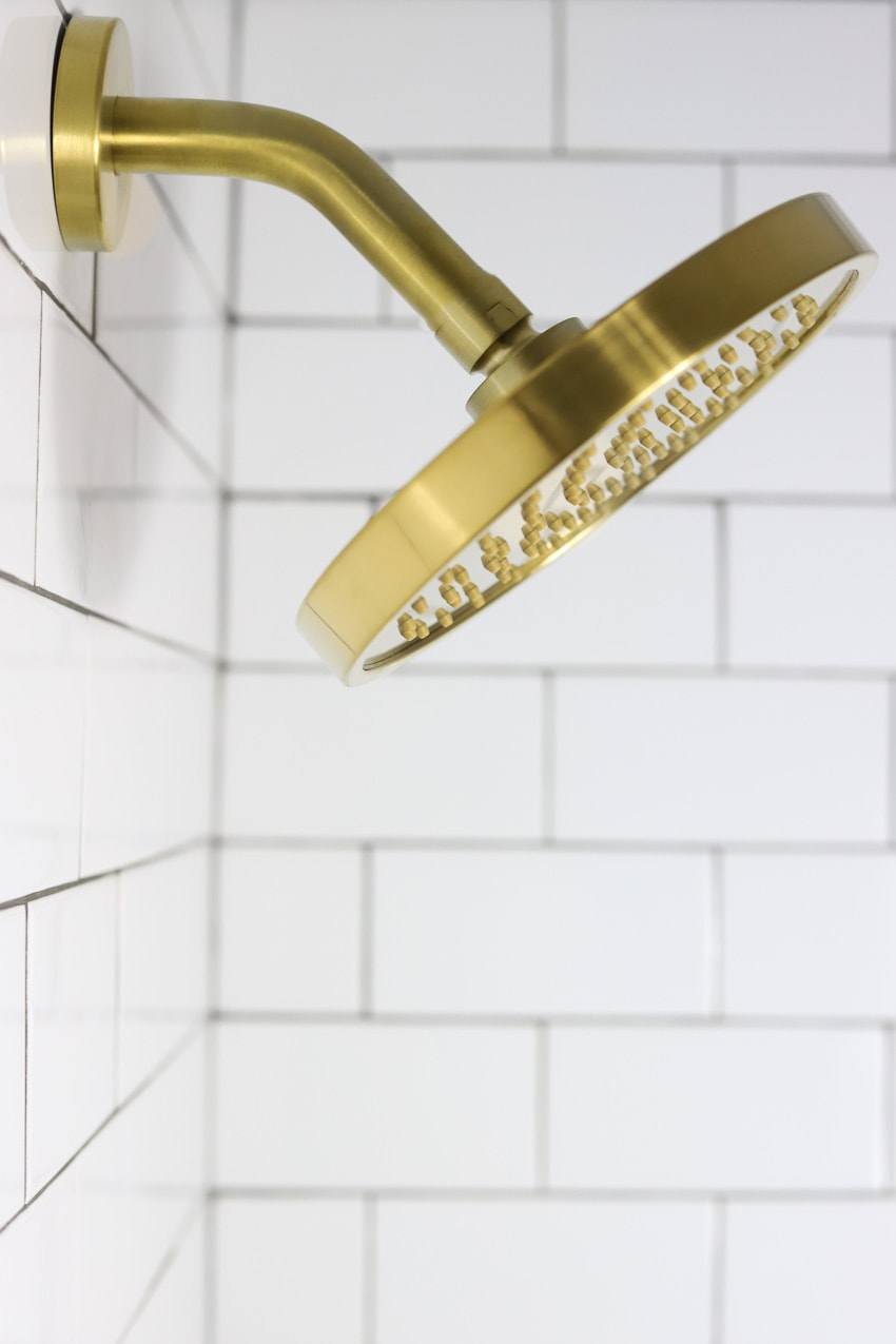 Gold shower head against white subway tile