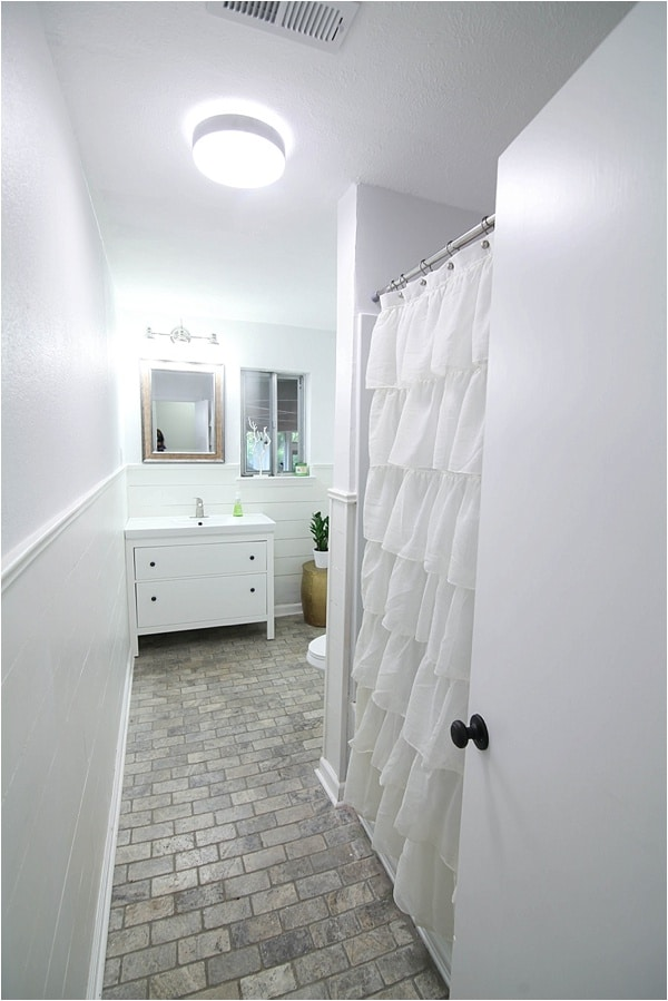 bathroom with light purple walls, ruffled shower curtain and white vanity with stone floor