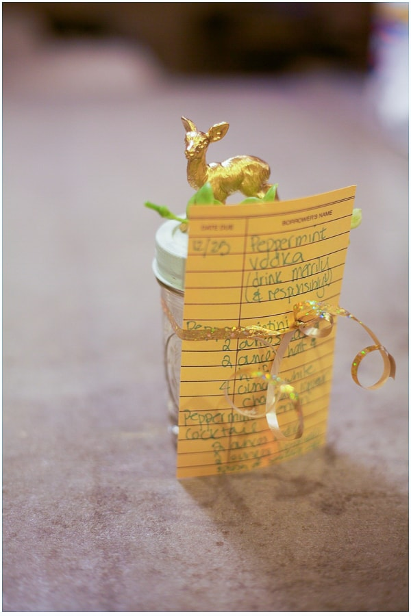 Mason jar filled with peppermint vodka with a recipe card tied to it. There's a gold deer glued to the top of the jar.