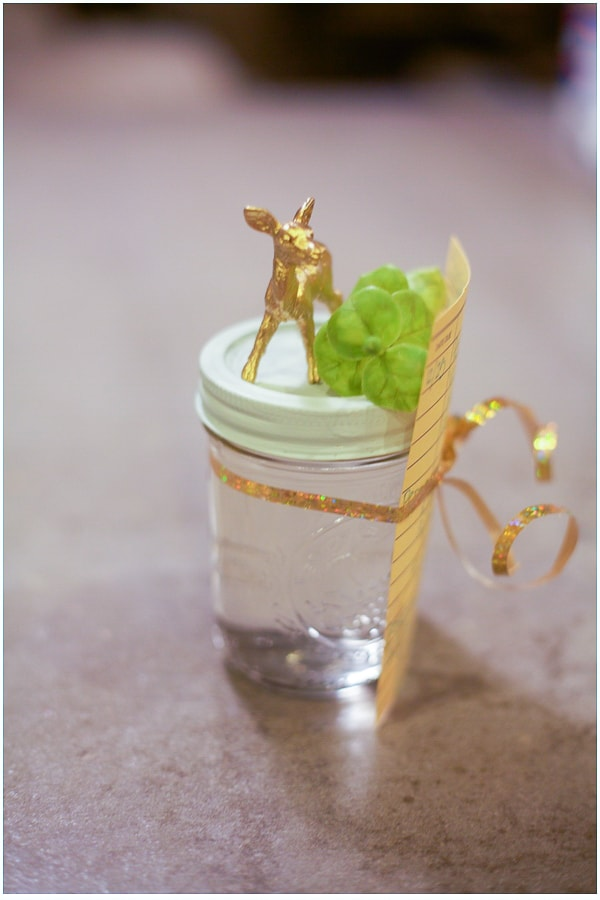 Mason jar with blue lid and clear liquid inside. The jar has a gold deer glued to the top