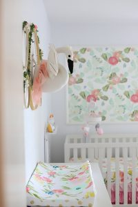 DIY nursery wall decor with flowers and a swan in a baby girl nursery with floral wallpaper in background