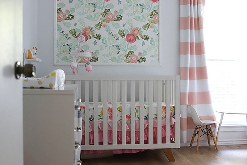 Baby girl nursery - floral theme with pink and white striped blackout curtains, white and wood dresser and crib, nursery wallpaper with florals