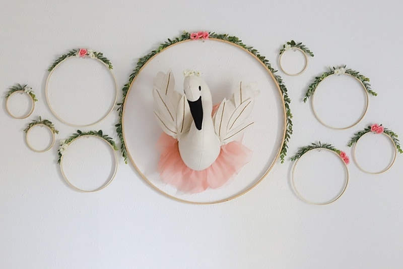 DIY nursery wall decor idea with floral hoops surrounding a faux swan bust wearing a tutu skirt